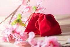红色礼物袋子和李子在老破旧的木表概念圣诞节和Newyear开花 图库摄影