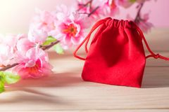 红色礼物袋子和李子在老破旧的木表概念圣诞节和Newyear开花 库存照片
