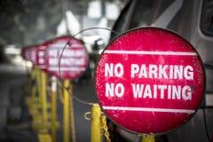 红色禁止停车在吉隆坡附近共同地被找到的等待的路标  免版税库存照片