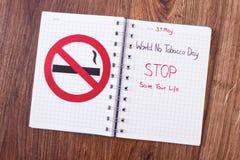 红色禁烟标志,世界在笔记本的没有烟草天 库存照片