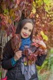 红色秋天叶子的俏丽的妇女 库存图片