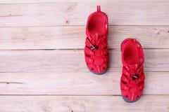 红色穿上鞋子在木背景的sandle 库存照片