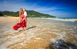 红色立场的白肤金发的妇女在海浪扣紧小女孩到乳房 库存照片