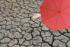 红色站立破裂的地球和韩上的人的伞和手 库存图片