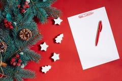 红色笔和笔记薄在用冷杉装饰的红色桌上分支 文本的背景 免版税库存图片