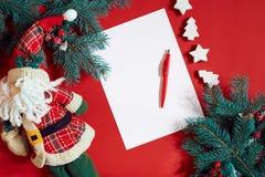红色笔和笔记薄在用冷杉装饰的红色桌上分支 文本的背景 库存图片