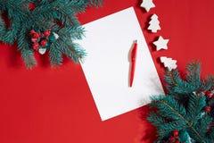 红色笔和笔记薄在用冷杉装饰的红色桌上分支 文本的背景 库存照片