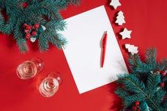 红色笔和笔记薄在用冷杉装饰的红色桌上分支 文本的背景 免版税库存照片