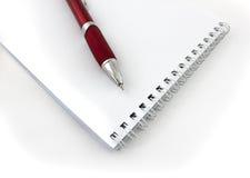 红色笔和笔记薄 库存图片