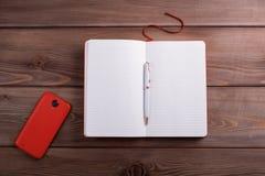 红色笔记本和一个智能手机在黑暗的木背景 免版税库存图片