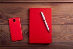红色笔记本和一个智能手机在黑暗的木背景 免版税库存照片
