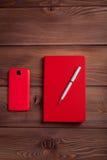 红色笔记本和一个智能手机在黑暗的木背景 库存照片