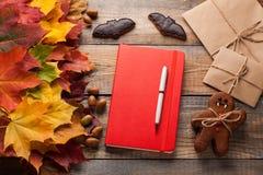 红色笔记本和曲奇饼为以棒和姜饼人吸血鬼的形式万圣夜在老木桌上 混杂的槭树autum 免版税库存照片
