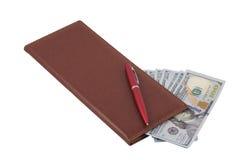 红色笔记本和金钱 免版税图库摄影