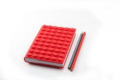 红色笔记本和铅笔在白色背景 免版税库存照片