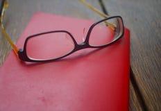 红色笔记本开放与在木桌上的玻璃 免版税库存照片