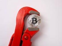 红色管子扳手夹紧一银币bitcoin 库存图片