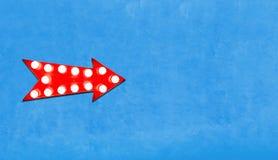 红色箭头在空的蓝色墙壁的左面塑造了与发光的电灯泡的葡萄酒五颜六色的被阐明的金属显示标志 免版税库存照片