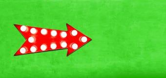 红色箭头塑造了与发光的电灯泡的葡萄酒五颜六色的被阐明的金属显示标志在主要空的鲜绿色墙壁上 免版税库存图片