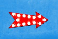 红色箭头塑造了与发光的电灯泡的葡萄酒五颜六色的被阐明的金属显示标志在生动的蓝色墙壁上 库存图片