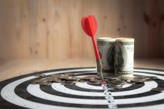红色箭箭头击中了掷镖的圆靶和金钱硬币的中心目标 库存图片