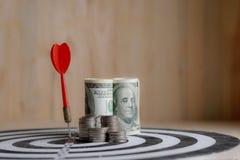 红色箭箭头击中了掷镖的圆靶和金钱硬币的中心目标 免版税图库摄影