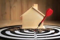 红色箭箭头击中了掷镖的圆靶的中心目标与房子的和 免版税库存图片