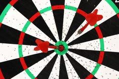 红色箭箭头在掷镖的圆靶背景的目标中心击中了 免版税库存照片