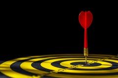 红色箭箭头在掷镖的圆靶的中心 隔绝在黑bac 库存图片