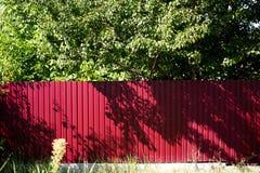 红色篱芭由金属制成在庭院里 库存图片