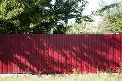 红色篱芭由金属制成在庭院里 免版税图库摄影