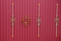 红色篱芭的片段有伪造的酒吧和一个美好的样式的 免版税库存照片