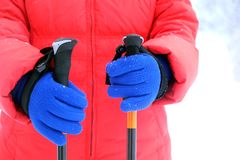 红色粗呢夹克和蓝色手套的人拿着远足的两根棍子 库存照片