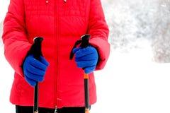 红色粗呢夹克和蓝色手套的人拿着远足的两根棍子 免版税库存图片