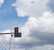 红色红绿灯有蓝天和雨云背景 免版税库存照片