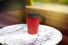 红色纸一次性咖啡对饭菜外卖点的在大理石桌上我 免版税库存照片