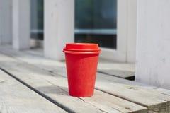 红色纸咖啡对饭菜外卖点的在咖啡馆之外的木地板上 在空气的早餐早晨 免版税库存照片