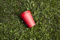 红色纸咖啡对饭菜外卖点的绿草草坪的 在咖啡馆之外的早餐早晨 库存图片