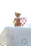 红色纸心脏和小棕色玩具熊由羊毛制成坐一块白色餐巾温暖的颜色 软绵绵地集中 免版税库存照片