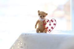 红色纸心脏和小棕色玩具熊由羊毛制成坐一块白色餐巾 颜色温暖 软绵绵地集中 库存照片