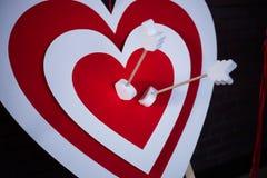 红色纸心脏在箭目标的中心 库存图片