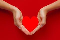 红色纸心脏在红色背景的手上 库存图片