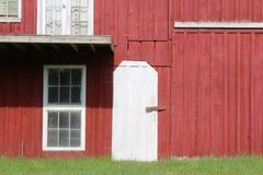 红色绘了有白色门和窗口修剪的谷仓 库存照片