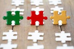 红色绿色和金拼图片断在老木头和绿色背景的 o 协会的标志和 免版税库存照片