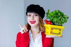 红色羊毛衫的妇女和帽子用草本和蕃茄以黄色 免版税库存照片