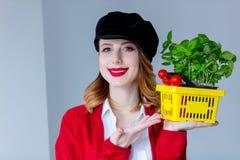 红色羊毛衫的妇女和帽子用草本和蕃茄以黄色 免版税库存图片