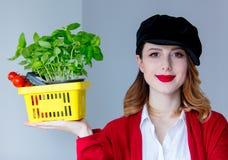 红色羊毛衫的妇女和帽子用草本和蕃茄以黄色 图库摄影