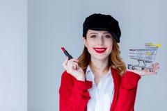 红色羊毛衫的有唇膏和推车的妇女和帽子 免版税图库摄影