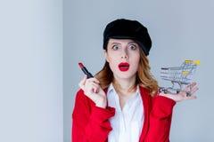 红色羊毛衫的有唇膏和推车的妇女和帽子 库存图片