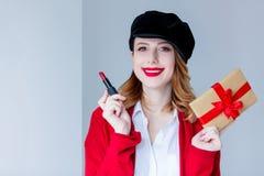 红色羊毛衫的有唇膏和礼物盒的妇女和帽子 免版税图库摄影